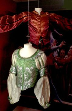 Image: two male ballet costumes on display, one is red and shiny, the other has white sleeves and an embroidered green body