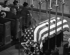 John F. Kennedy's coffin lies covered in an American Flag in St. Matthew's Cathedral in Washington, D.C. on November 25, 1963 while funeral attendees look on somberly.