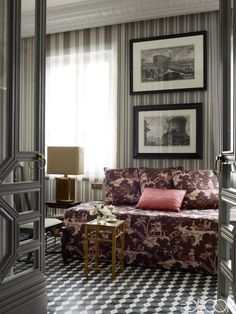 A pair of 18th-century engravings by Piranesi hangs above a daybed upholstered in a Jim Thompson toile de Jouy in the guest bedroom. The bamboo side table is from the 1970s, the wallpaper is by Ralph Lauren Home, and the doors are painted in Farrow & Ball's Down Pipe. - ELLEDecor.com (=)