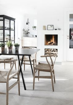 Nordic dining space with a bright and simple fireplace built into the wall and a small space for storage of the firewood.