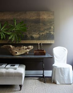 simple and chic - large piece of driftwood juxtaposed against elegant furniture, antique artwork, gray walls