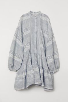 Oversized tunic in airy woven cotton fabric with a small ruffled collar. Buttons at front heavily dropped shoulders and long sleeves with narrow cuffs with buttons. Wide flounces at hem. Cocktail Dress Attire, Ruffle Neck Blouse, African Maxi Dresses, Indian Blouse, Mode Hijab, Tunic Tops, Clothes, Woven Cotton, Cotton Fabric