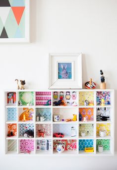 craft paper for the back of the shelves adds pop and character to a boring shelves