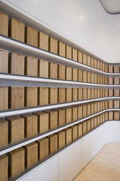 Wall with wooden boxes inside the Friedrichstadtapotheke by Wiewiorra Hopp Architekten.