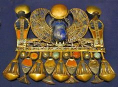 Egyptian pectoral were decorative pendants worn by Egyptians. Either wore them around neck as brooch feature symbols such as scarabs or uraeus.