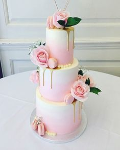 Three tier wedding cake with soft pink ombré, gold drip, macarons and fresh flowers / foliage