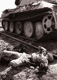 A dead German tank crewman lies on railroad tracks by his knocked out Panzer tank.
