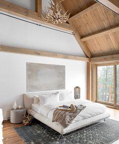 Malgré la hauteur spectaculaire du plafond cathédrale, la charpente en bois crée un cocon chaleureux à l'étage, où se trouve la chambre principale.