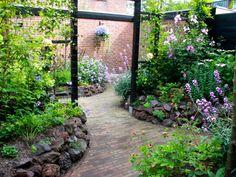 intieme kleine achtertuin met veel bloemen. Ontwerp staat op de volgende pin.