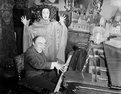 """W.T. Benda Playing Piano to Woman in Mask Original caption: 10/19/1941- DISCORD- Wearing a """"jester"""" mask, Mr. W.T. Benda dashes off a little number on the piano. The lady audience is wearing a realistic mask of """"Fury"""" and one doesn't need a blueprint to understand her attitude towards Mr. Benda's musical efforts. These two masks fit the action ideally. 19 October 1941"""