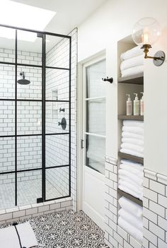 Patterned tile bathroom with steel shower doors. Globe wall sconce - white towels. White subway tile bathroom