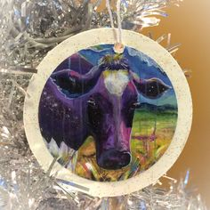 """Every tree needs a purple cow ornament!  I use an archival Epson print of my own artwork and adhere it to a painted wooden ornament. I seal the print and add a touch of sparkle with glitter paint. My logo is stamped on the back. Each ornament measures 3"""" in diameter and the print is 2.5"""" in diameter.  Your ornament can come in a clear bag tied with curling ribbon for $10 or in a gift box for $12."""