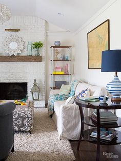 Stripping away the tile and paneling from the fireplace revealed a pleasant surprise: an old brick wall, which was dressed up with white paint, a floating mantel, and a wallmount art lamp. Vaulting the ceiling furthered the airy design. Built-ins were replaced with furniture for a less formal, more flexible look. Colorful pillows and accessories add pop.