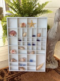What a gorgeous white wood case for displaying your collection of seashells, miniatures, wine corks or any small collectible. Several size openings from very small to large. Hangs vertical but hooks can be changed out to hang horizontally. In very good clean condition! Makes a wonderful statement to any bedroom, bathroom or entryway. Seashells are for display only & not for sale. Ready to hang with attached hooks  Measures 24 height x 16.75 wide x 15 deep total, 39 total openings 1 large ...