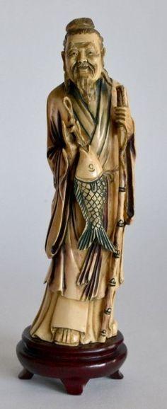 SUJET en ivoire sculpté, sage barbu tenant un poisson. H. 25 cm