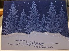 """By Tamie Ackerson. Stamp tree from """"Lovely as a Tree"""" by Stampin' Up in VersaMark on blue card front and heat emboss with white powder.(Or just stamp with white ink.) Cut white cardstock piece 5 1/2"""" x 3"""" then tear unevenly into 2 pieces. Apply glue to torn edge then dip in Dazzling Diamonds or other glitter. (Save other torn piece for a second card.) Stamp sentiment. Attach white piece to card. Add falling snow with white gel pen."""