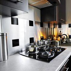 Une crédence en carreaux aluminium adhésif avec un jeu de carreaux adhésif noir qui fait un rappel des couleurs dominantes de la cuisine noi...