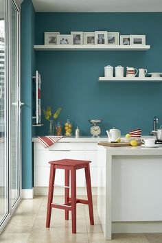 Teal/turquoise wall with white gallery shelves