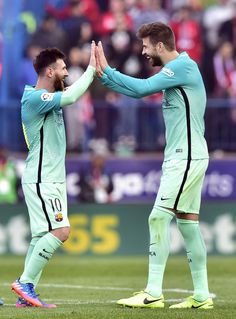 Barcelona's Argentinian forward Lionel Messi (L) celebrates with Barcelona's defender Gerard Pique at the end of the Spanish league football match Club Atletico de Madrid vs FC Barcelona at the Vicente Calderon stadium in Madrid on February 26, 2017. / AFP / GERARD JULIEN