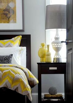 Love the bedding   Atmosphere Interior Design    Gorgeous gray & yellow contemporary bedroom with gray walls paint color, espresso stained wood bed & nightstand, yellow vases, white lamp and yellow & gray duvet & shams bedding.