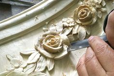 Carving of a custom designed mantel by Auffrance.Custom mantel with rosé garlands & insignia being hand carved for a Boiserie living room. Designed & manufactured by Auffrance.