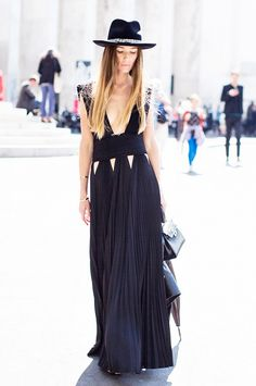 A black deep V, pleated maxi dress is worn with a black accessories like the hat, bag and shoes.