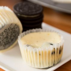 This is a photo of delicious oreo cheesecake cupcakes with an oreo hiding on the bottom
