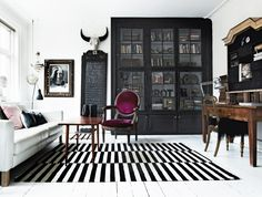 wielka czaszka + białe ściany + czarna witryna + dywan w biało-czarne pasy + krzesło vintage + kryształowe żyrandole