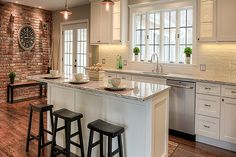 white Shaker kitchen cabinets with center island, subway tile backsplash, and expanses of windows create a bright kitchen