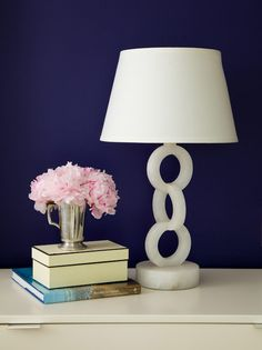 Stunning vignette featuring cobalt blue walls as backdrop for an exquisite vintage alabaster chain link lamp with white lampshade, and mercury glass vase with a splash of pink floral.