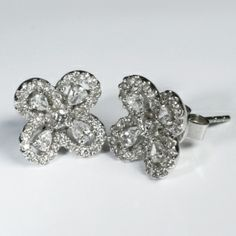 Diamond Flower Earrings  A beautiful pair of diamond set earrings. The earrings have been designed in the shape of a flower using brilliant and pear cut diamonds. The total weight of the diamonds set in these stunning earrings is 1.0ct. The earrings have been hand made in 18ct white gold. Total weight of the earrings is 4.6gms.