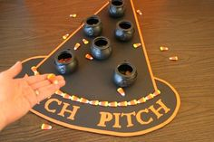 halloween game witch pitch, tossing candy corns into cauldrons