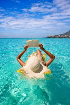 Reading in the water on a resort by the beach. This is perfect way to relax in the summer! #indigo #perfectsummer