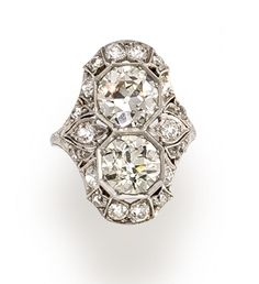 An art deco diamond ring, circa 1920  centering two vertically-set old European-cut diamonds within an openwork and millegrained surround of smaller old European-cut diamonds; central diamonds weighing approximately: 1.60 and 1.50 carats; remaining diamonds weighing approximately: 1.00 carat total; mounted in platinum; size 5