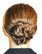 twisty chignon: Separate out a small section of hair about 1/4 inch thick. Using the thumb and index finger of both hands, begin to twist this section tightly until it begins to coil up upon itself. Let this hair continue to coil up upon itself close to the head, and then bobby-pin the twisted hair in place next to your. Continue this process all around the ponytail.