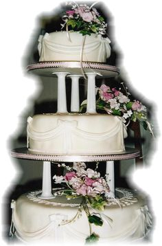 Wedding Fruit Cake with marzipan and white sugarpaste. Drapes & ribbons and replica bride's bouquet on each layer. Set on pillars.