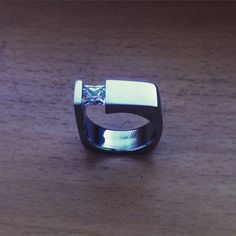 Stainless steel ring with tension set princess gem