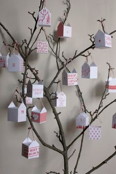 paper houses tied with bakers twine to a branch for advent
