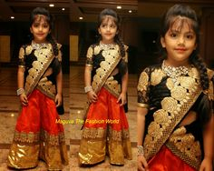 Cute kid in Orange half saree with golden border,paired up with black floral duppata and black net floral blouse