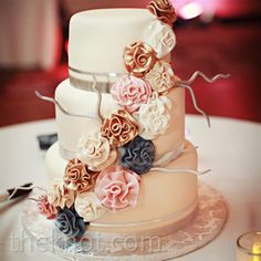 Sugar flowers and branches covered all three tiers of the white-fondant cake.