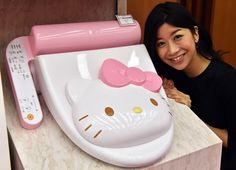 An employee for Japanese character goods maker Sanrio displays a prototype model of a Hello Kitty branded toilet seat at Sanrio's headquarters in Tokyo on February 2, 2015. The device has seat heating and warm water shower functions.