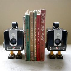 Outdated (yet adorable) vintage cameras enjoy a new spotlight as bookends. repurposed vintage Kodak Bakelight cameras, along with mah jong tiles and dominos, to create chic and stylish camera bookends. Old Cameras, Vintage Cameras, Antique Cameras, Brownie Hawkeye Camera, Blue Velvet Chairs, Dollar Stores, Thrift Stores, Decoration, Bookends