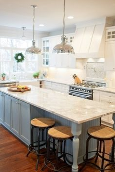 source: Britt Lakin Photography  Two-tone kitchen with white shaker cabinets paired with Vermont White Granite Countertops and subway tiled backsplash. Industrial pendants over blue kitchen island with beadboard trim, white granite countertops lined with