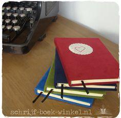 Gelinieerde A6 boekjes met harde kaft bekleed met synthetisch suède. Voorop een rondje van oud boekenpapier, vastgenaaid met een hartje. Verschillende kleuren beschikbaar. Mail info@schrijf-boek-winkel.nl