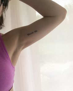 Minimalist arm tattoo, typewriter font; shine on.