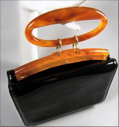 """""""Back to back"""" purse in genuine patent leather. Lucite handle adds appeal to this petite purse. Both interiors and inside flaps are lined in dark brown genuine leather. One interior has a small open sidewall pocket. 7.5"""" W x 5"""" H"""