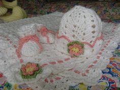blanket pattern - www.Bernat.com.  Bernat Softee Baby-Blanket and Booties. I didn't use this bootie pattern because I didn't know if we were getting a girl or a boy when I started the project. The hat is at this website: http://www.toastyfrog.net/2009/12/25/baby-ripple-hat-crochet-pattern/, and the flower is here:http://attic24.typepad.com/weblog/crochet-flowers-and-leaves.html. I added the pink trim to the hat and changed the border of the blanket so I could add the yarn ribbon.