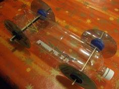 Rubberband Powered Pop Bottle Car Components - 2 litre pop bottle (Chassis) - 4 CDs or DVDs (Wheels) - Wooden spoon (Drive axle) - Wooden skewer (Front axle)...