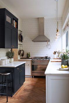 The new classic kitchen: dark navy cabinetry, brass pulls, brass modern fixtures, wood texture, subway tile.