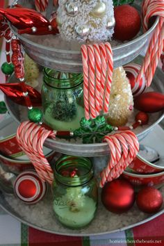 Easy and festive centerpiece with a galvanized 3 tier stand, layered with rock salt, candy canes, ornaments and and bottle brush trees in green Ball jars   homeiswheretheboatis.net #Christmas #tablescape